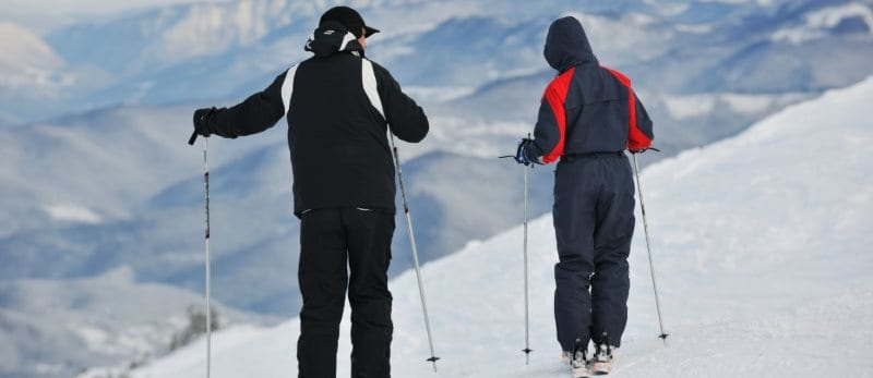 two people with skis looking over a mountain