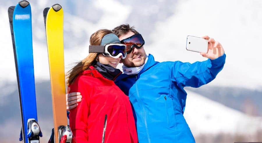 young couple skiing with their cell phone